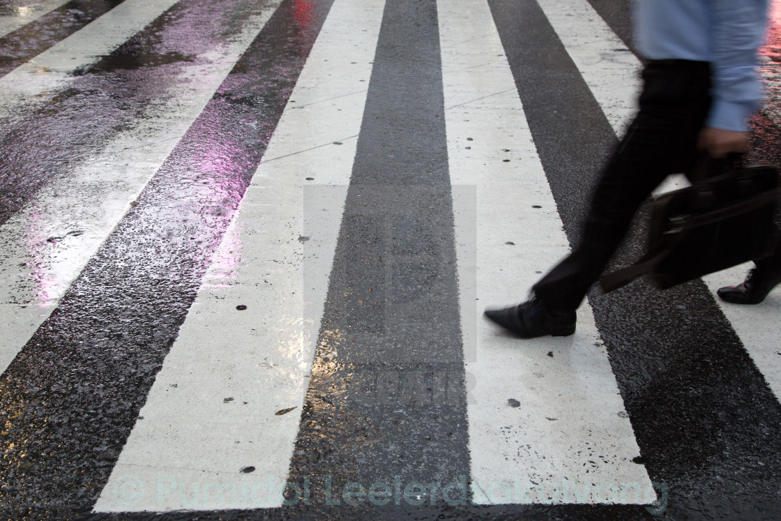 """Business people cross road in the rain"" stock image"