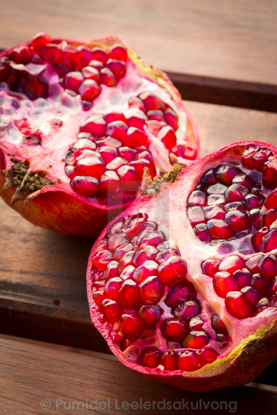 """Red juicy pomegranate fruit on wooden table"" stock image"