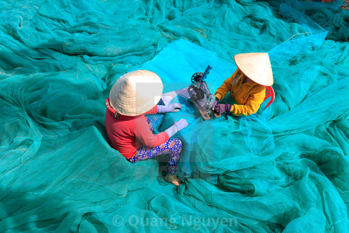 """two women are sewing fishing nets in fishing village"" stock image"