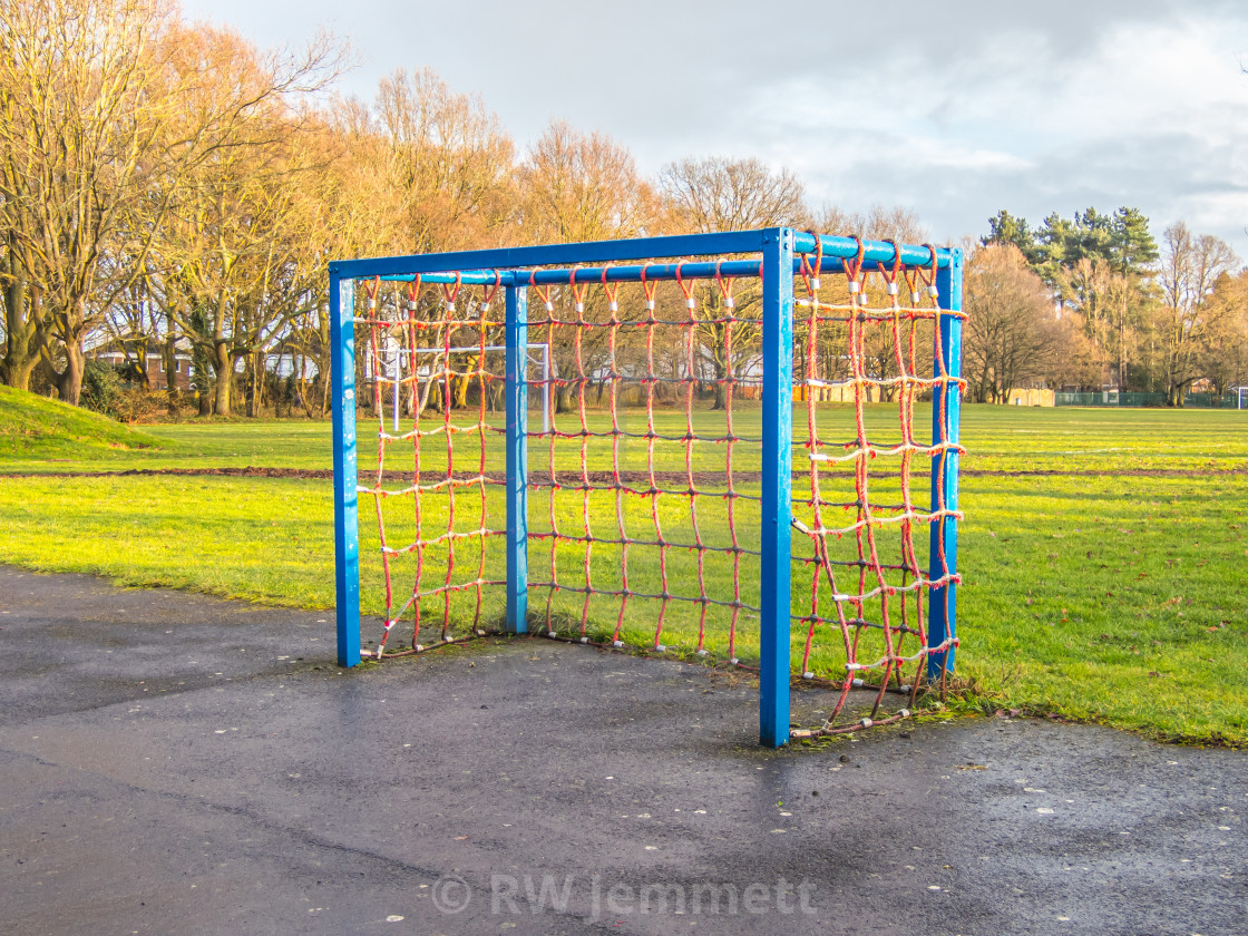 """A small blue goal in a park with red netting"" stock image"