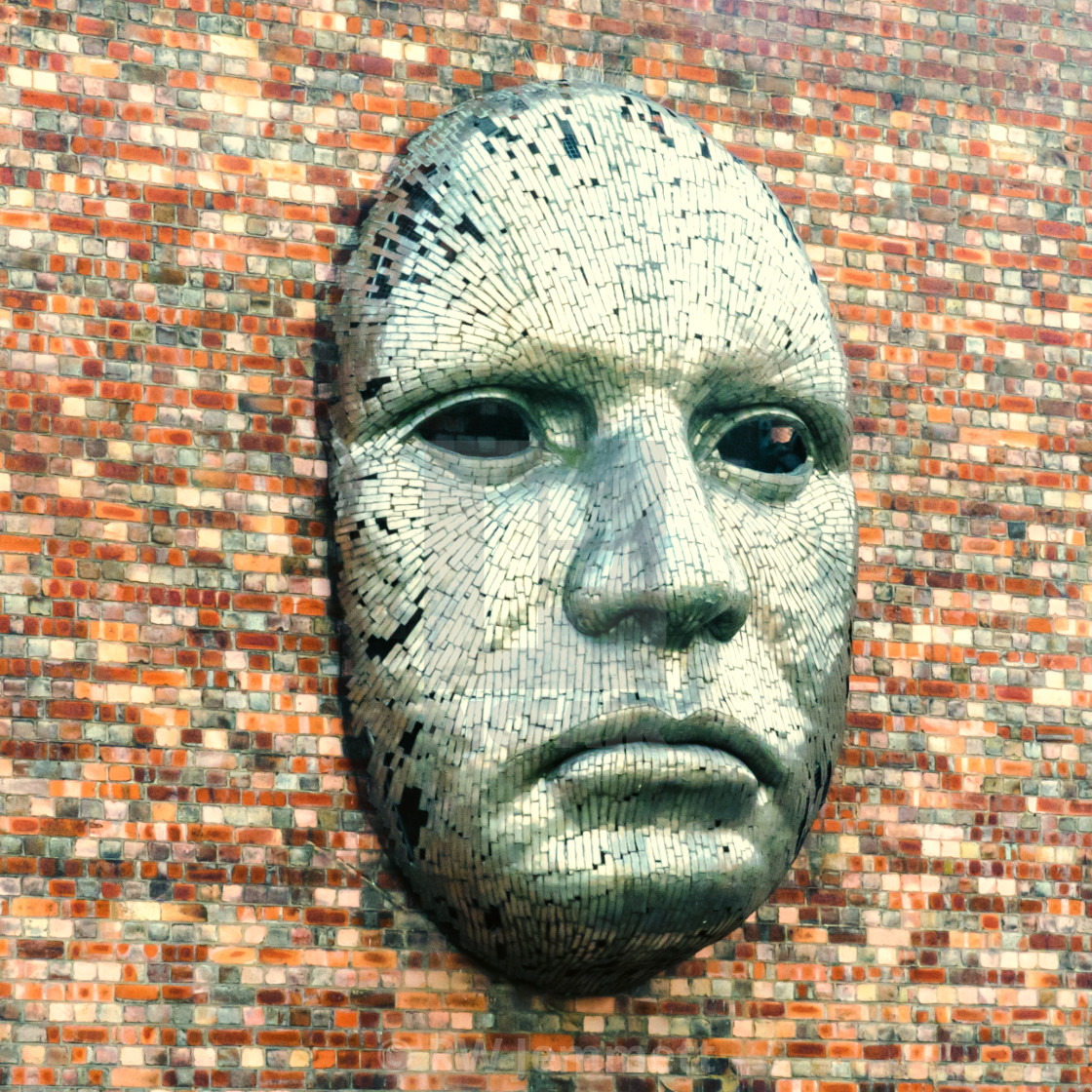 """Metal face sculpture on the outside wall of Drill Hall"" stock image"