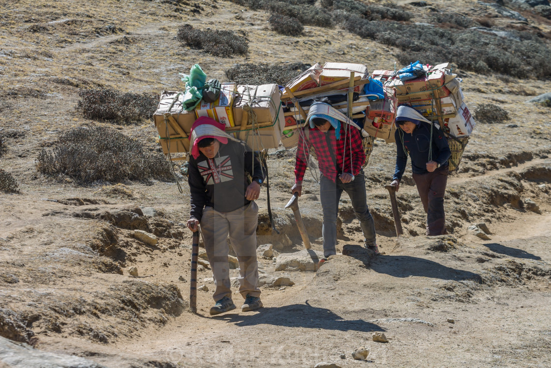 """Porters carrying a heavy loads en route towards the Everest Base Camp"" stock image"