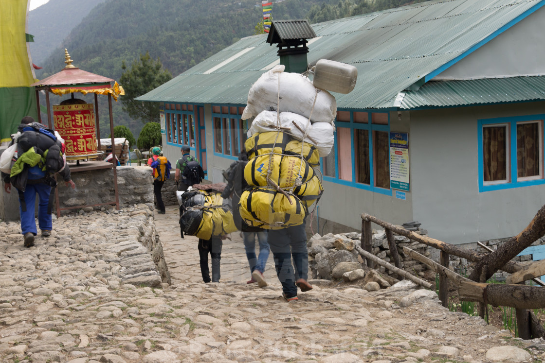 """Porter carrying a heavy loads on the Everest Base Camp trekking route"" stock image"