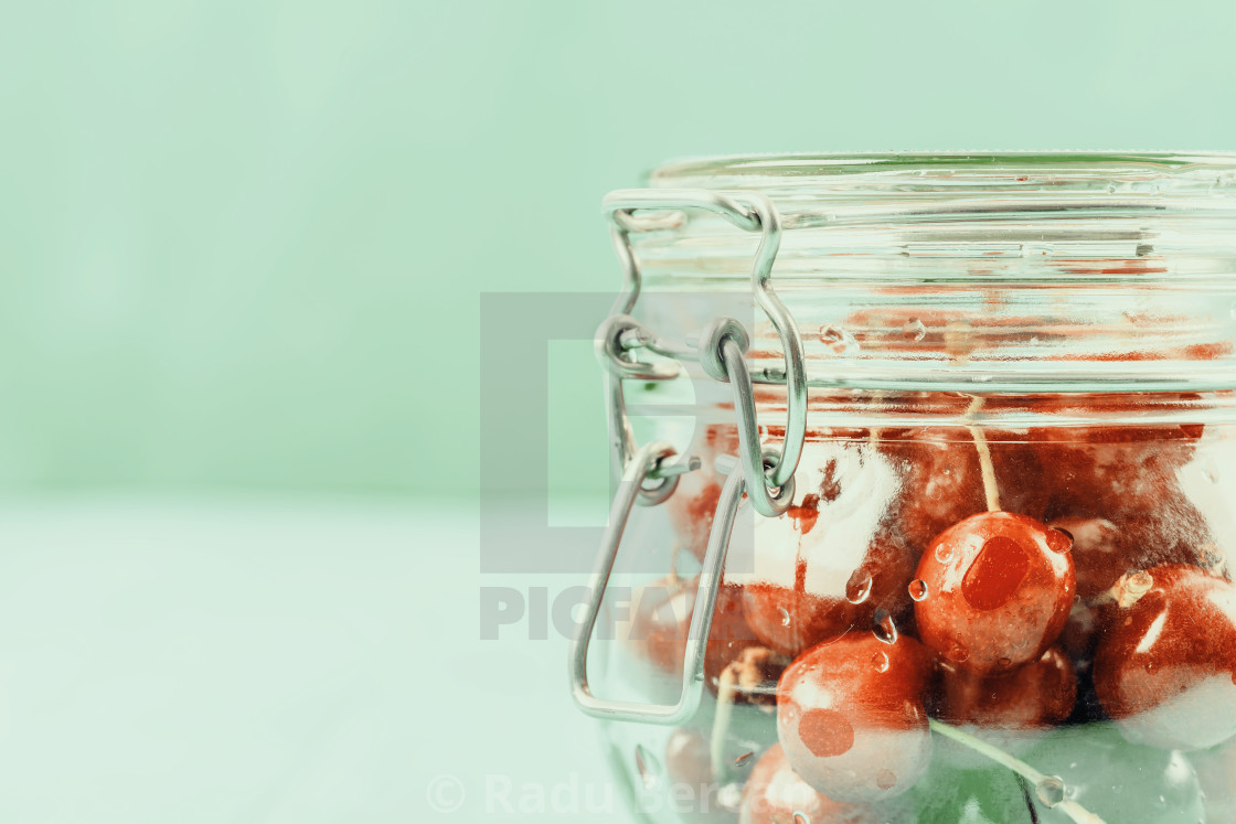 """Jar Of Red Fresh Cherries On Turquoise Background"" stock image"