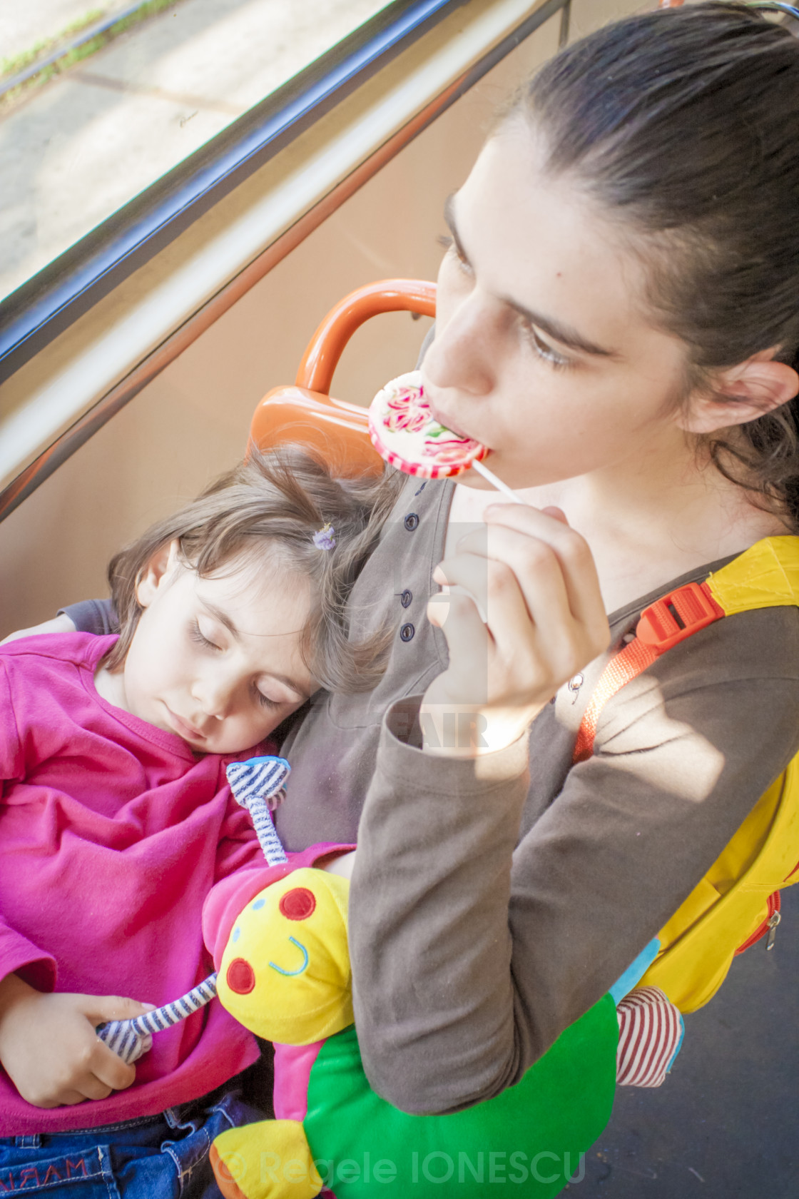 """Mother Holding Sleeping Toddler Eating Lollipop"" stock image"