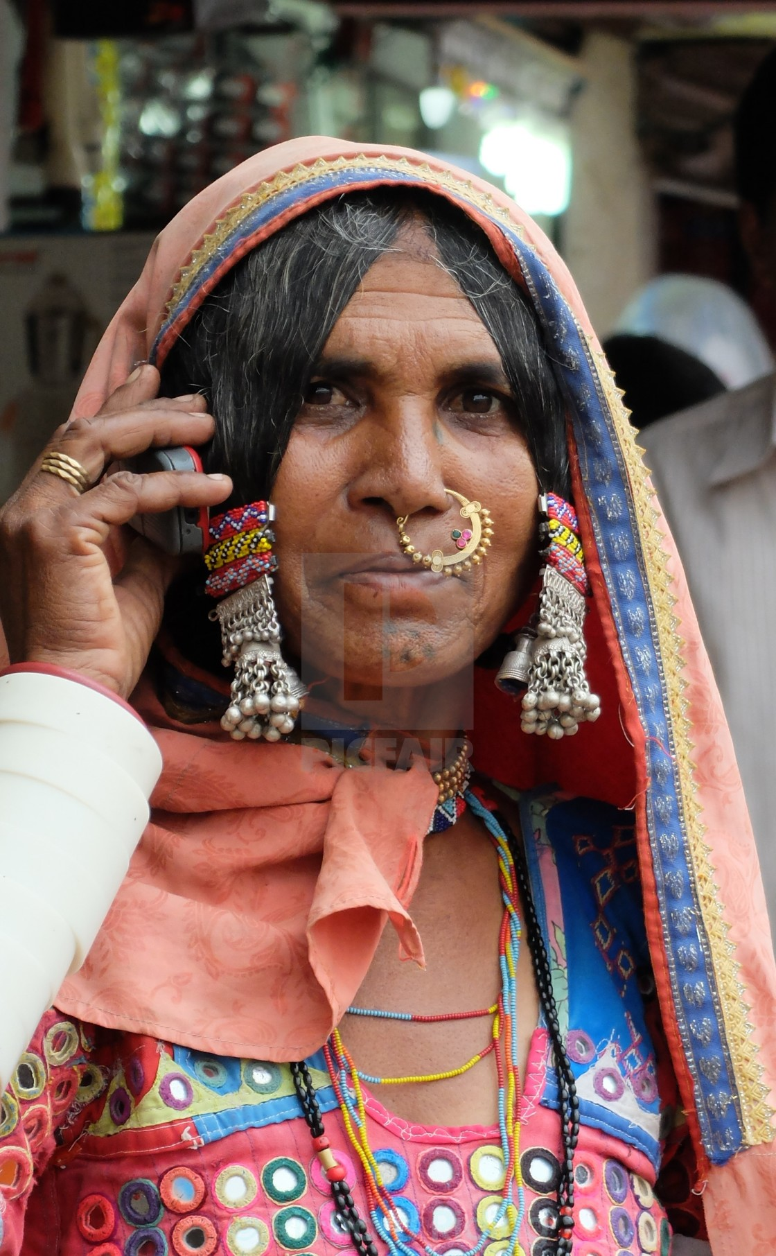 """Tribal Woman on mobile - Southern India"" stock image"
