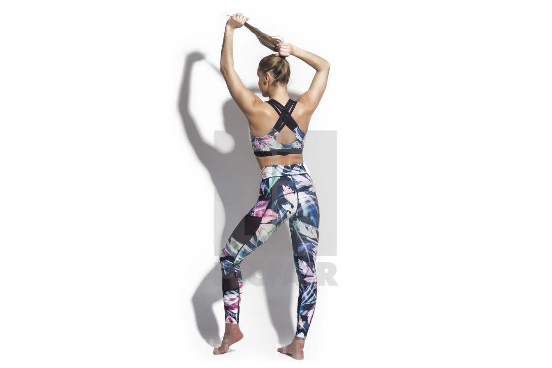 """woman wearing colourful sportswear, leggings and sports bra."" stock image"