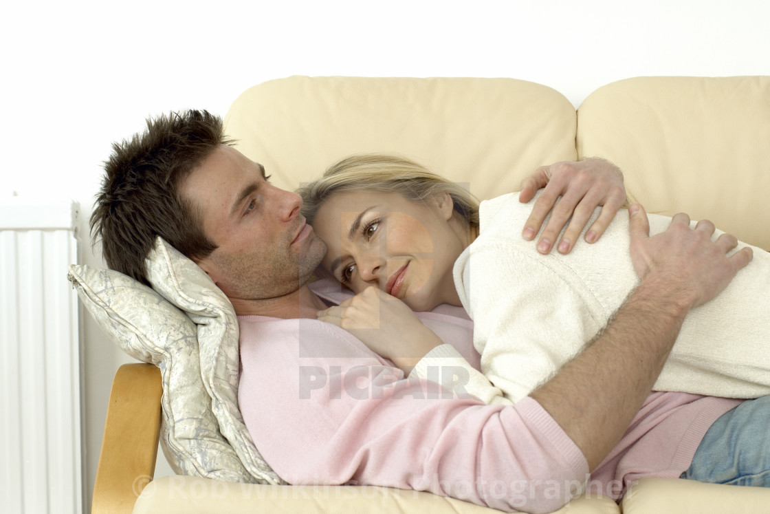 Couple Cuddling Up On A Sofa   License, Download Or Print ...