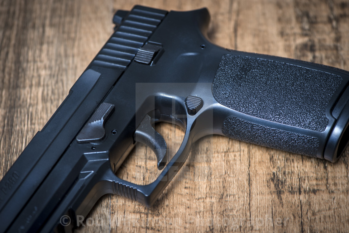"""a Sig P250 semi-automatic pistol on wooden surface"" stock image"