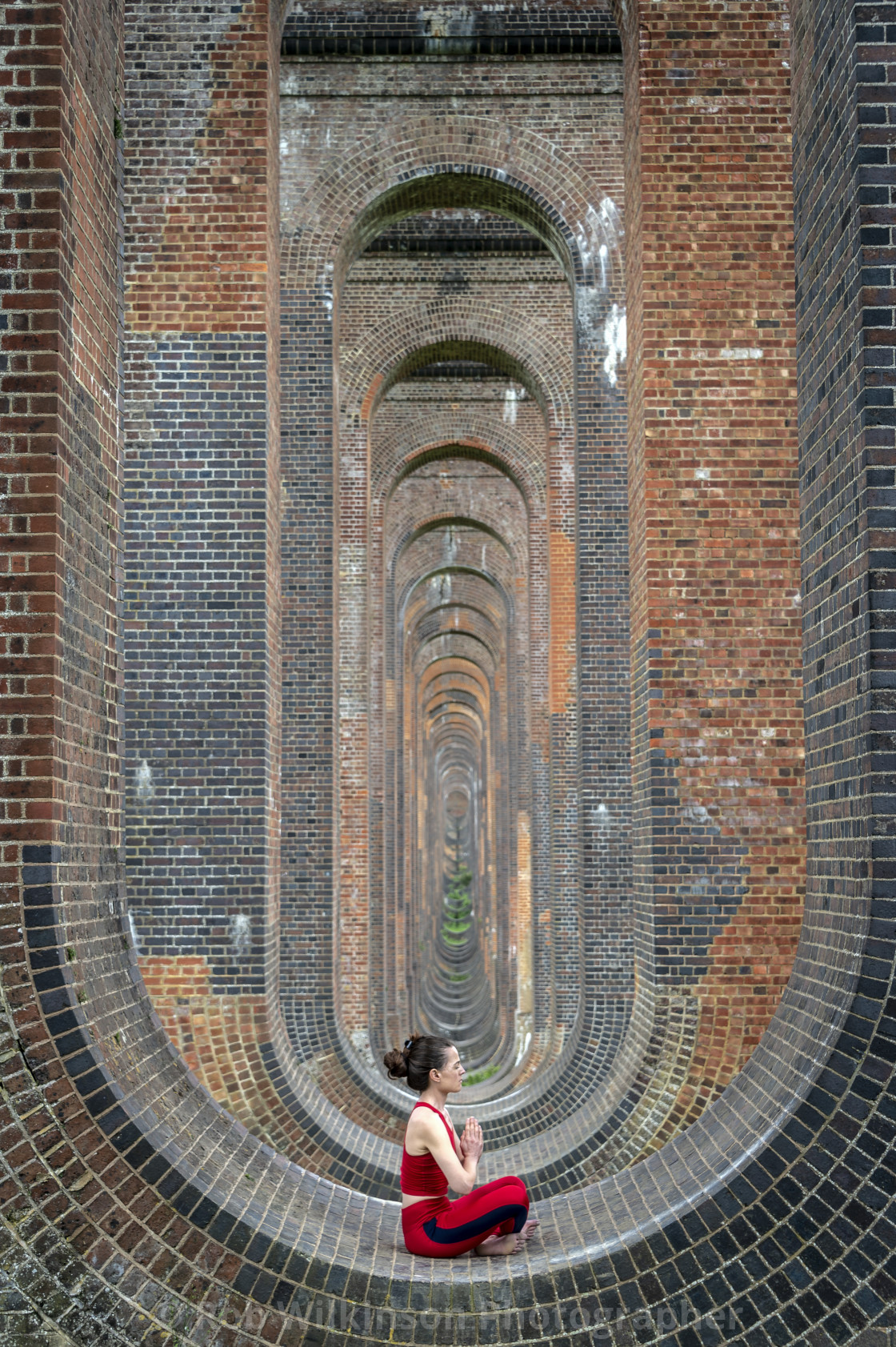 woman sitting in the arches of the Ouse Valley Viaduct