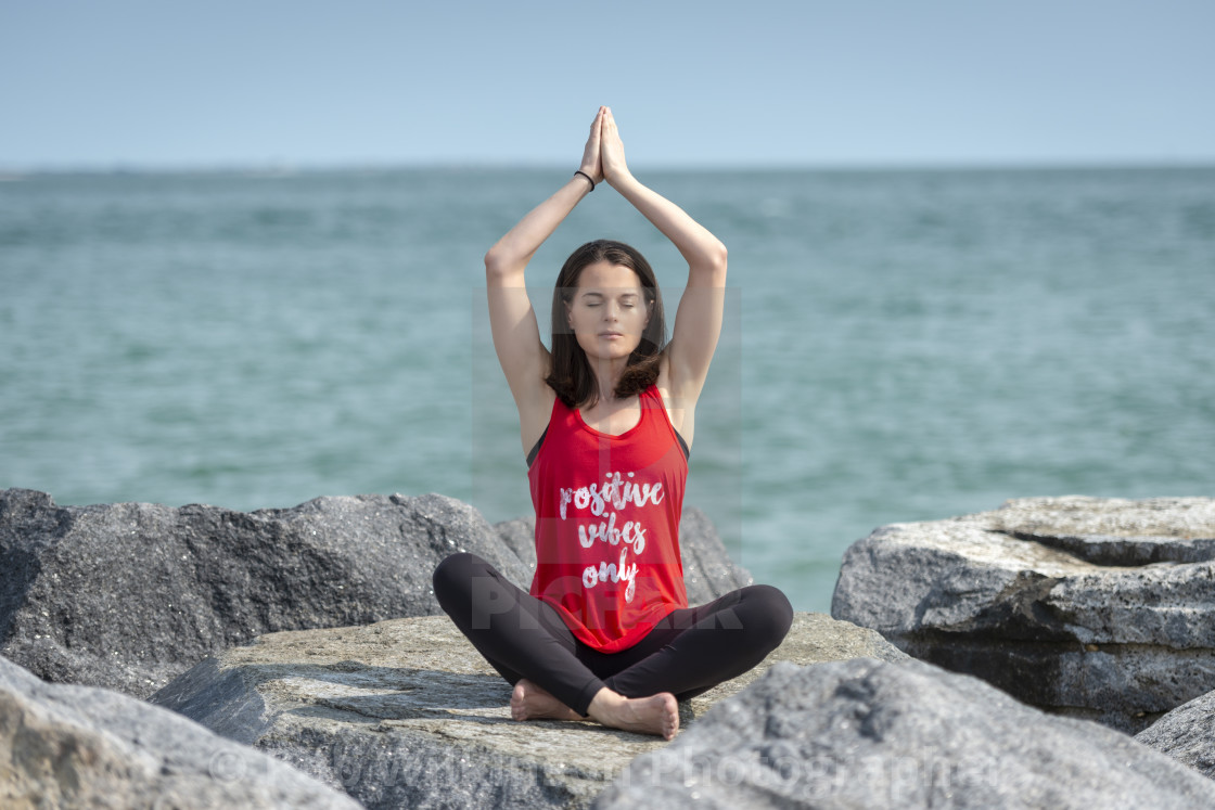 """woman sitting crossed legged on rocks practicing yoga, easy pose, wearing a t shirt with 'Positive vibes only' slogan."" stock image"