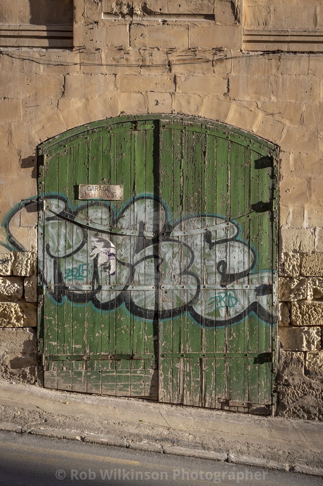 """old weathered green garage door in a street in Silema, Malta."" stock image"