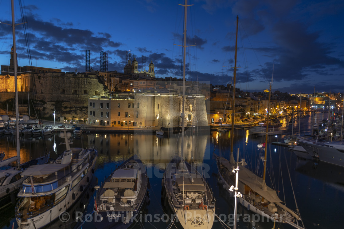 """View across the harbour from Vittoriosa to Senglea at dusk with yachts moored."" stock image"