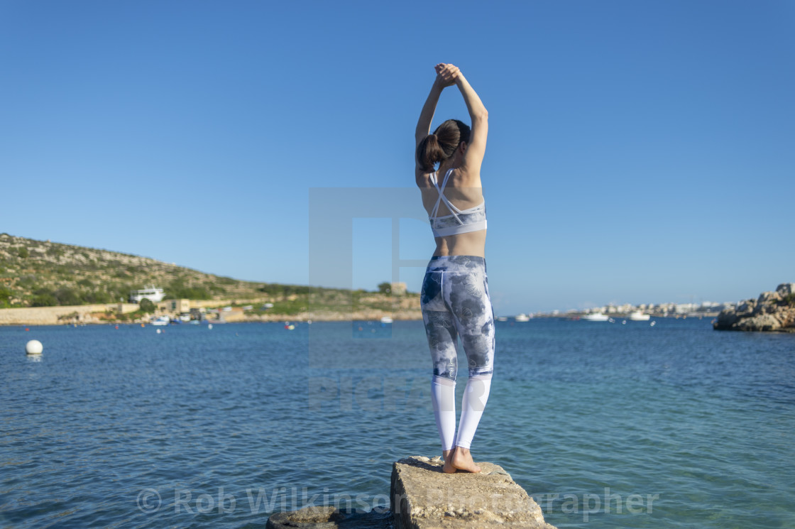 """woman doing stretching execises by the sea, back view"" stock image"