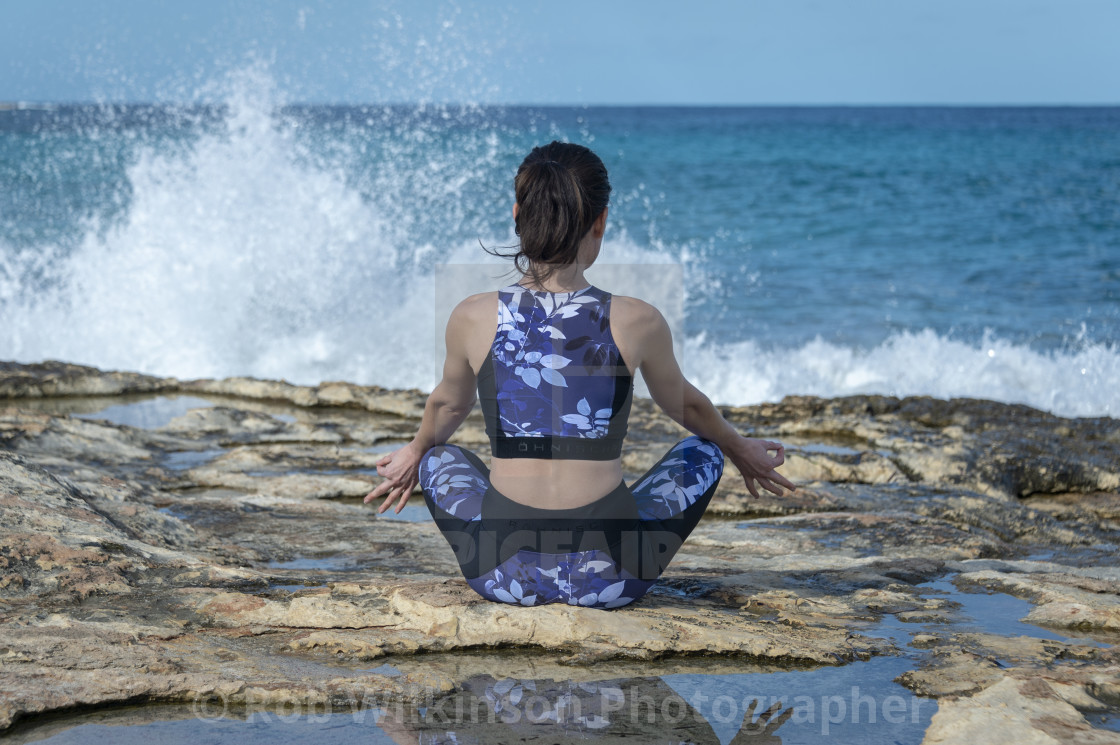 """woman sitting on the rocks practicing yoga with crashing waves"" stock image"