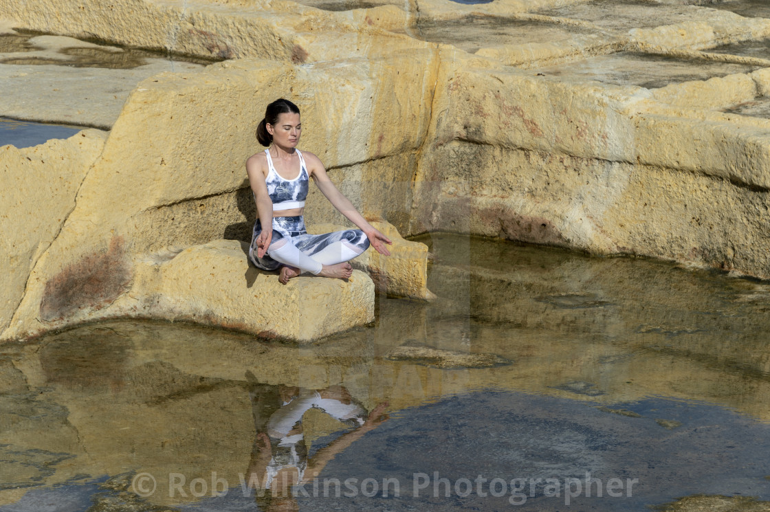 """woman meditating, practicing the 'easy pose' amongst the limestone salt pans in Malta"" stock image"