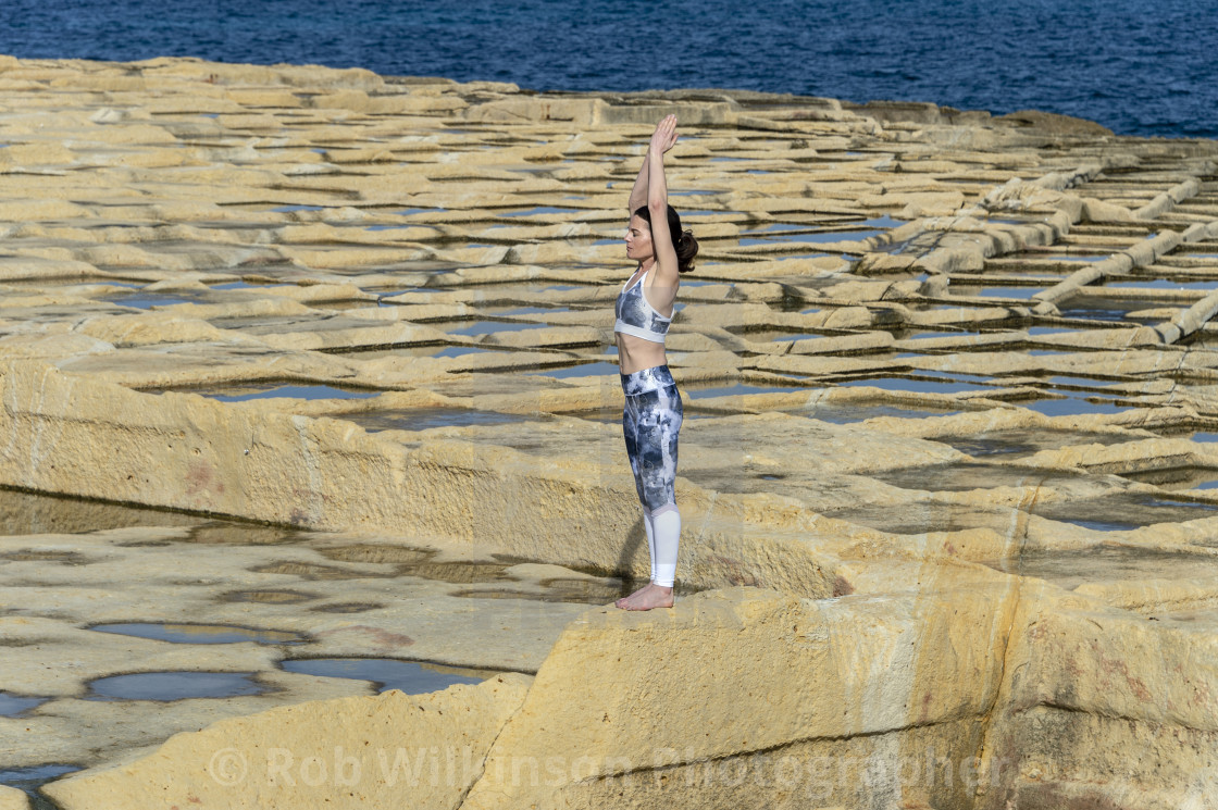 """woman meditating, practicing the 'mountain pose' amongst the limestone salt pans in Malta"" stock image"