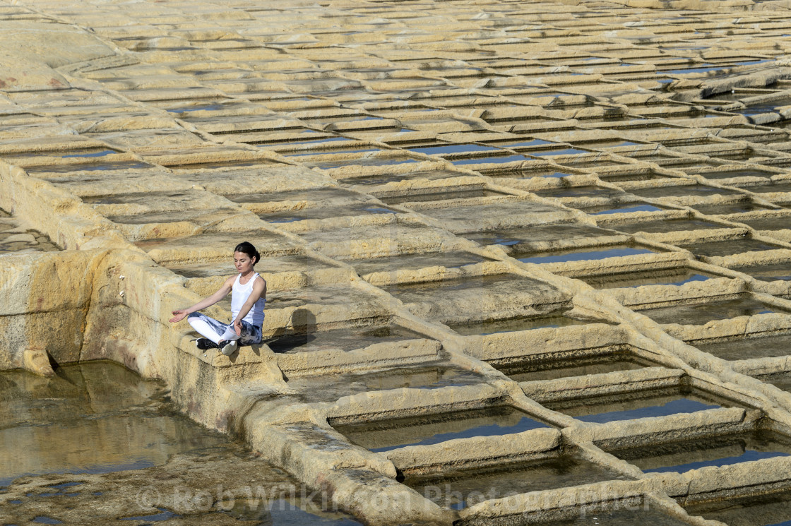 """woman meditating, sitting amongst the limestone salt pans in Malta"" stock image"