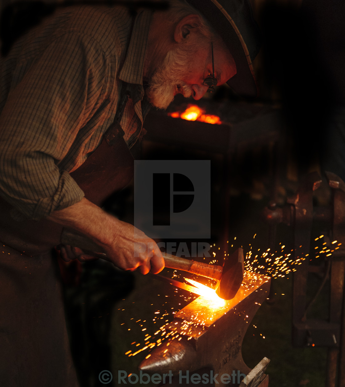 """Blacksmith working at his anvil"" stock image"
