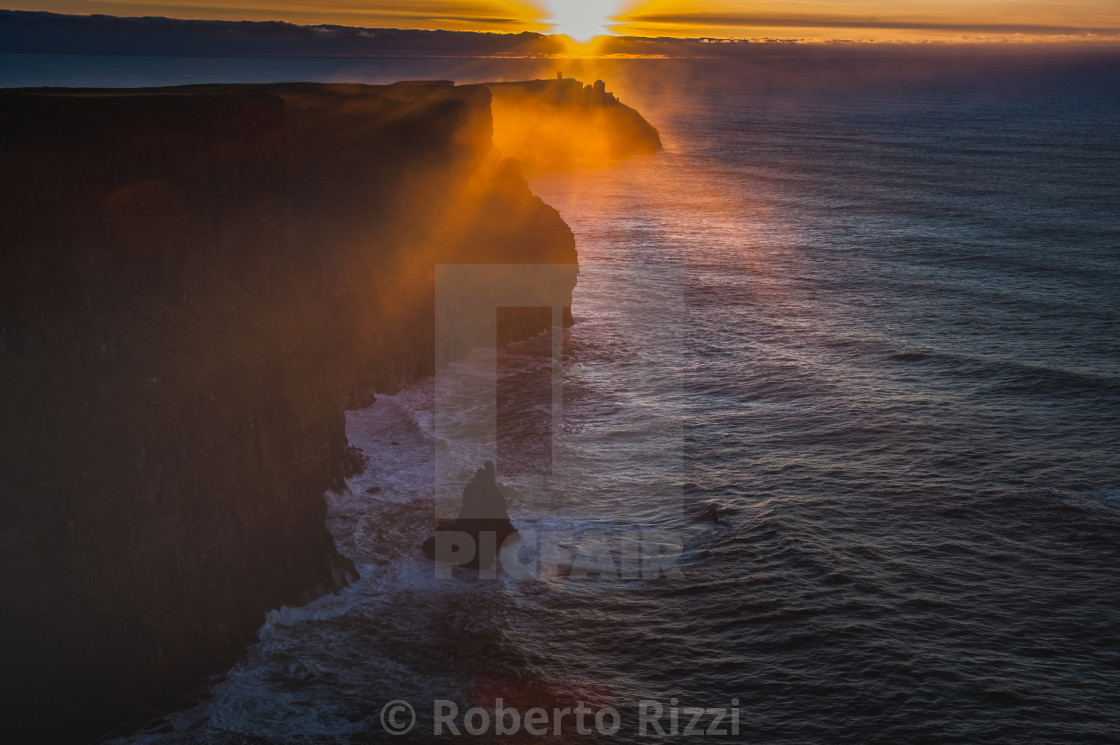 """Sun sets on the Cliffs of Moher, Ireland"" stock image"