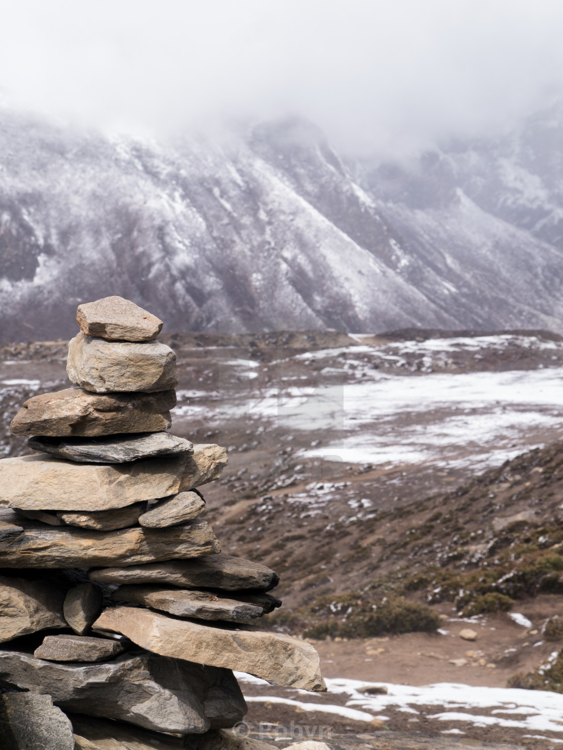 """Stone Marker Pile in Snowy Himalayan Mountains"" stock image"