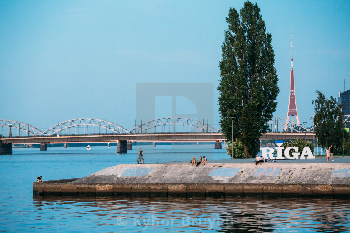 """Riga Latvia. Embankment At Daugava River With City Name Sign, Resting People..."" stock image"