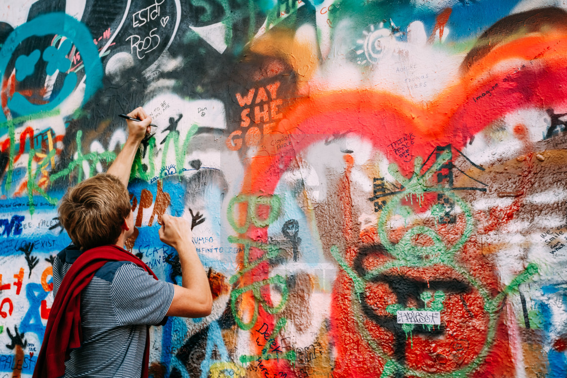 Woman draws on the john lennon wall in prague czech republic stock image