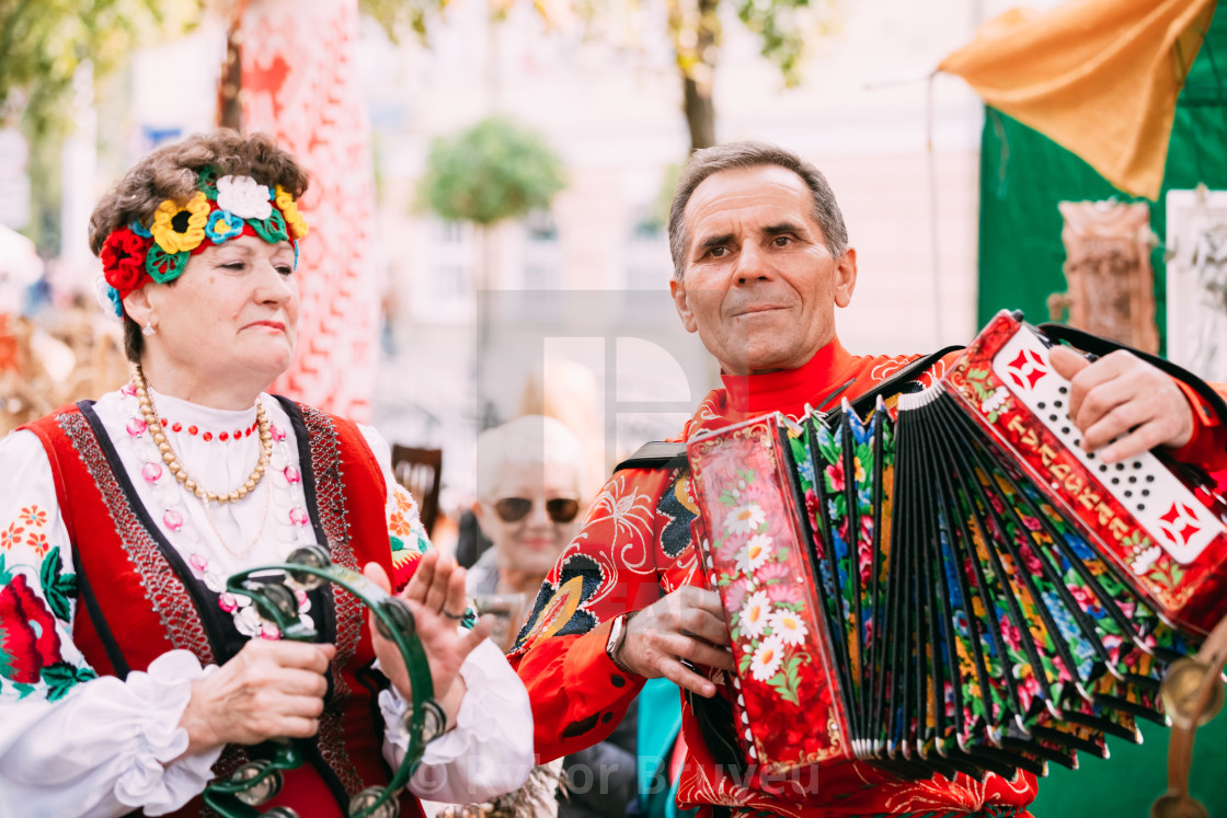 Unknown man in national clothes plays the accordion folk Belarusian