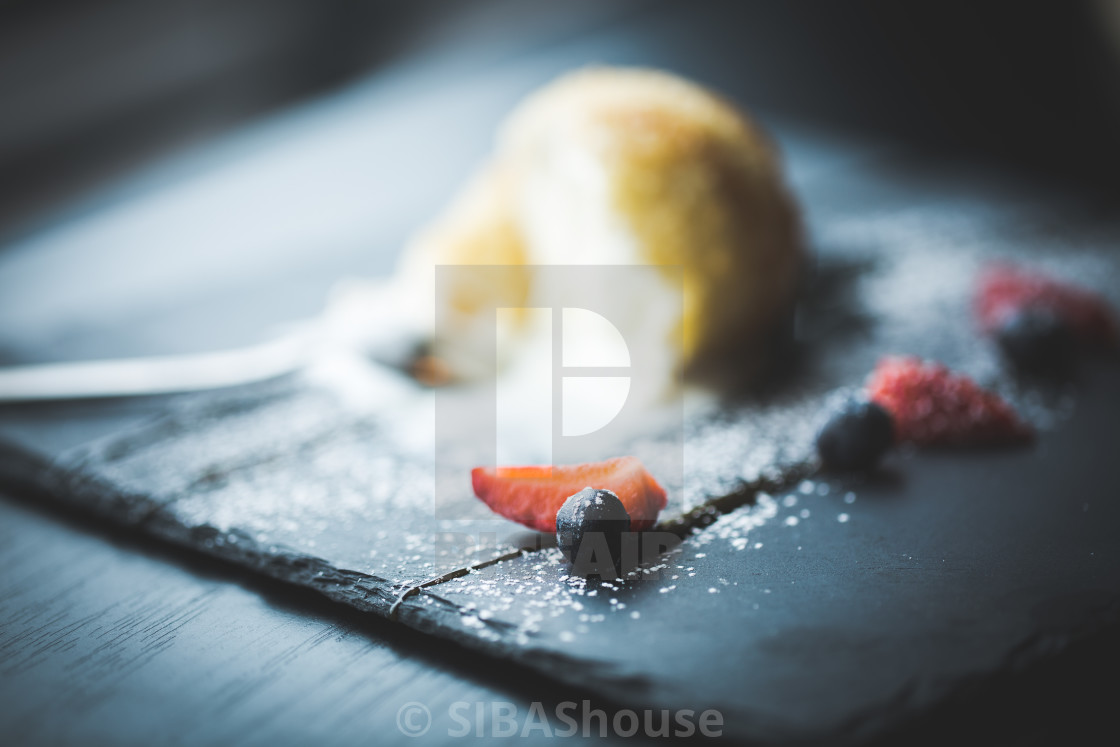 """Grilled ice-cream in coconut with sauce on black stone plate. Asian food background. Eating concept. Restaurant place with wooden table. Copy space for text, design."" stock image"