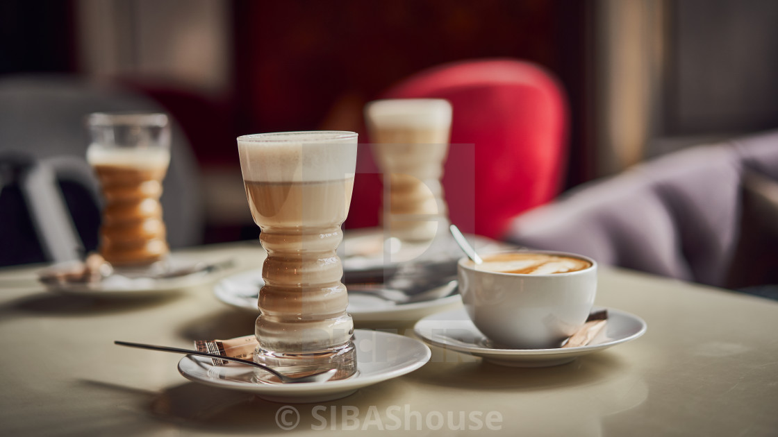 """""""Latte glass with layered latte, cappuccino or mocha with foam on table in..."""" stock image"""