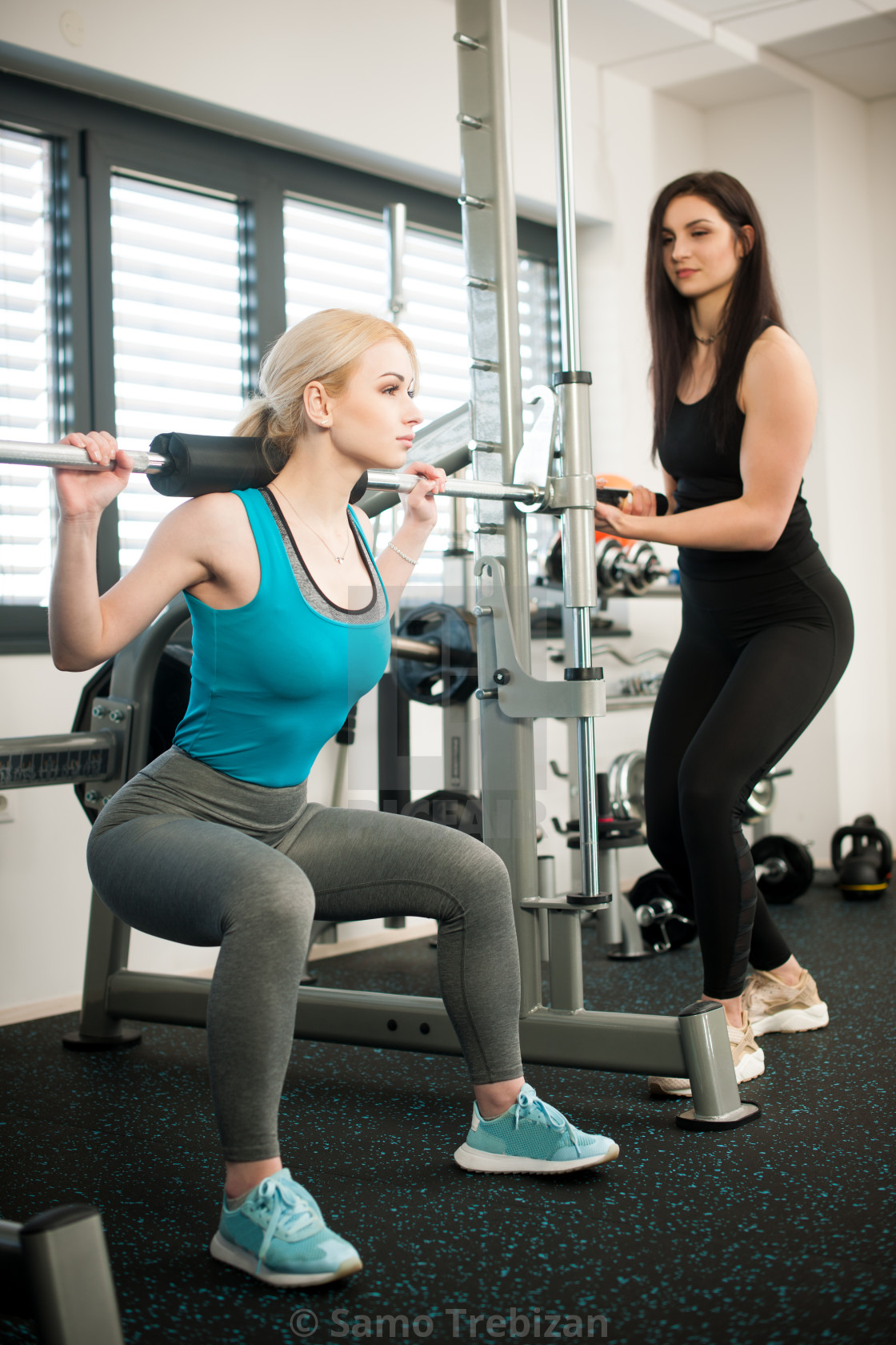 Beautiful young woman workout in fitness gym doing weighted squats ...