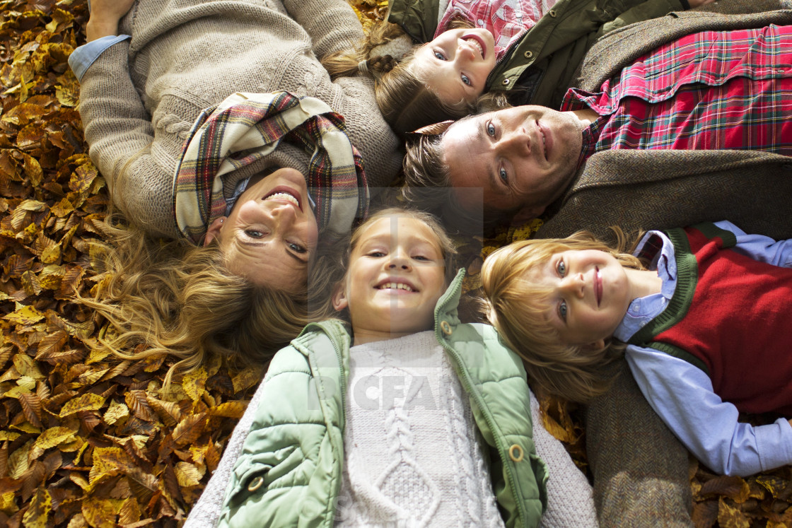 """Family lying down on Autumn leaves"" stock image"