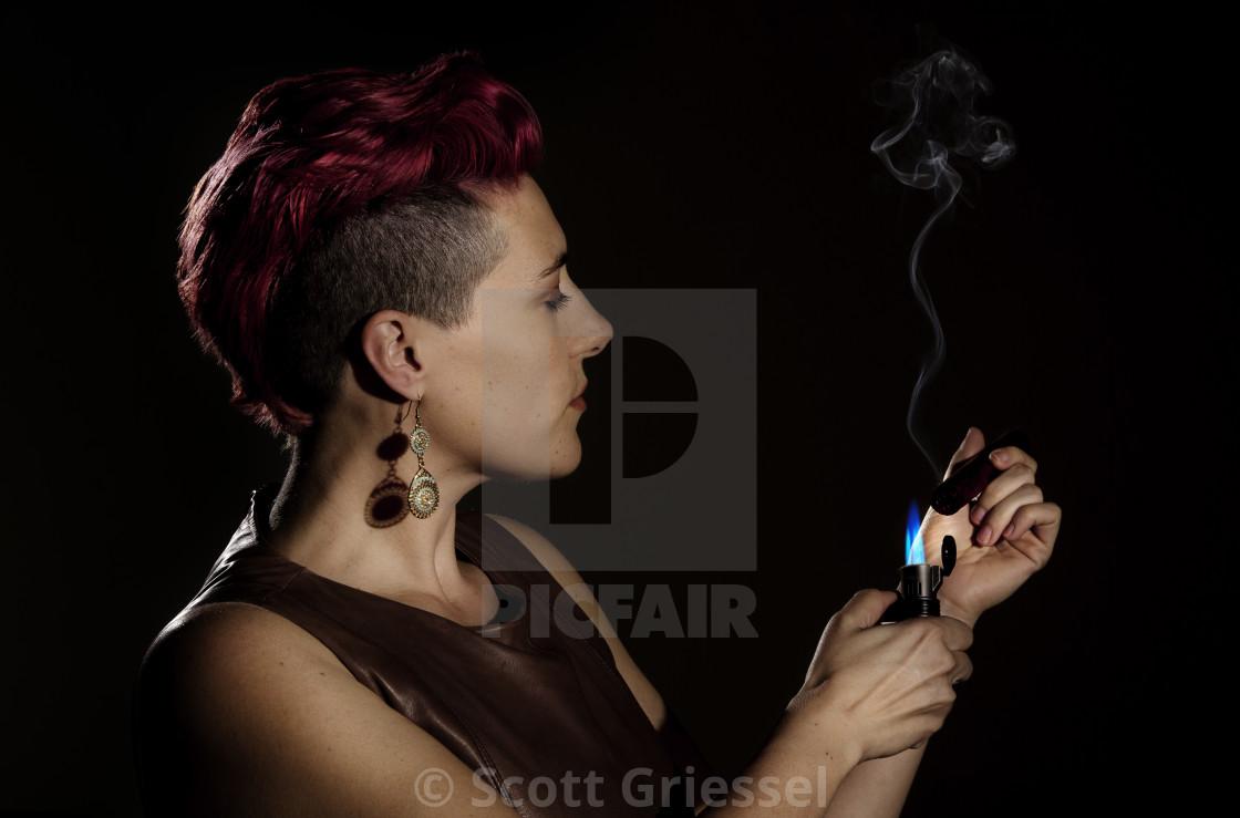 """Modern Woman Lighting a Cigar"" stock image"