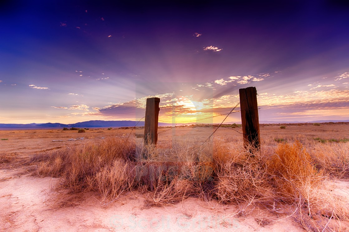 """Desert fence at dawn with God rays"" stock image"