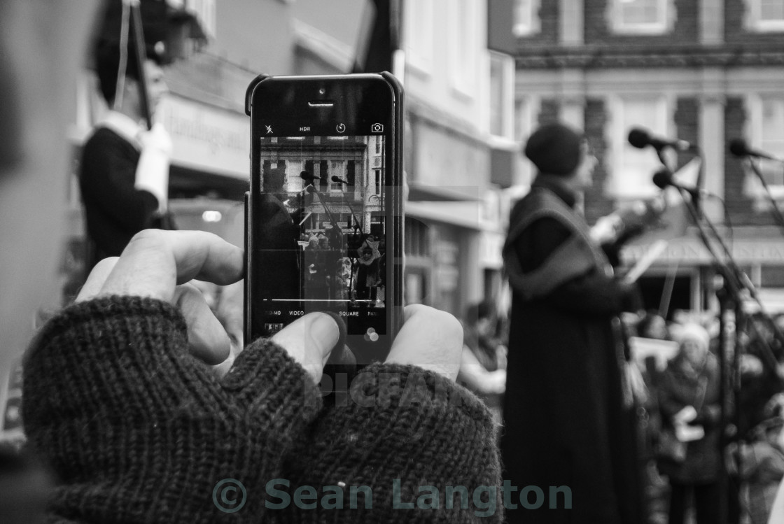 """Man Takes a Photo on His Phone At A Rally"" stock image"