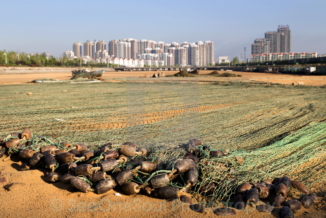 """Fishing Nets on the Beach with the City in the Background"" stock image"