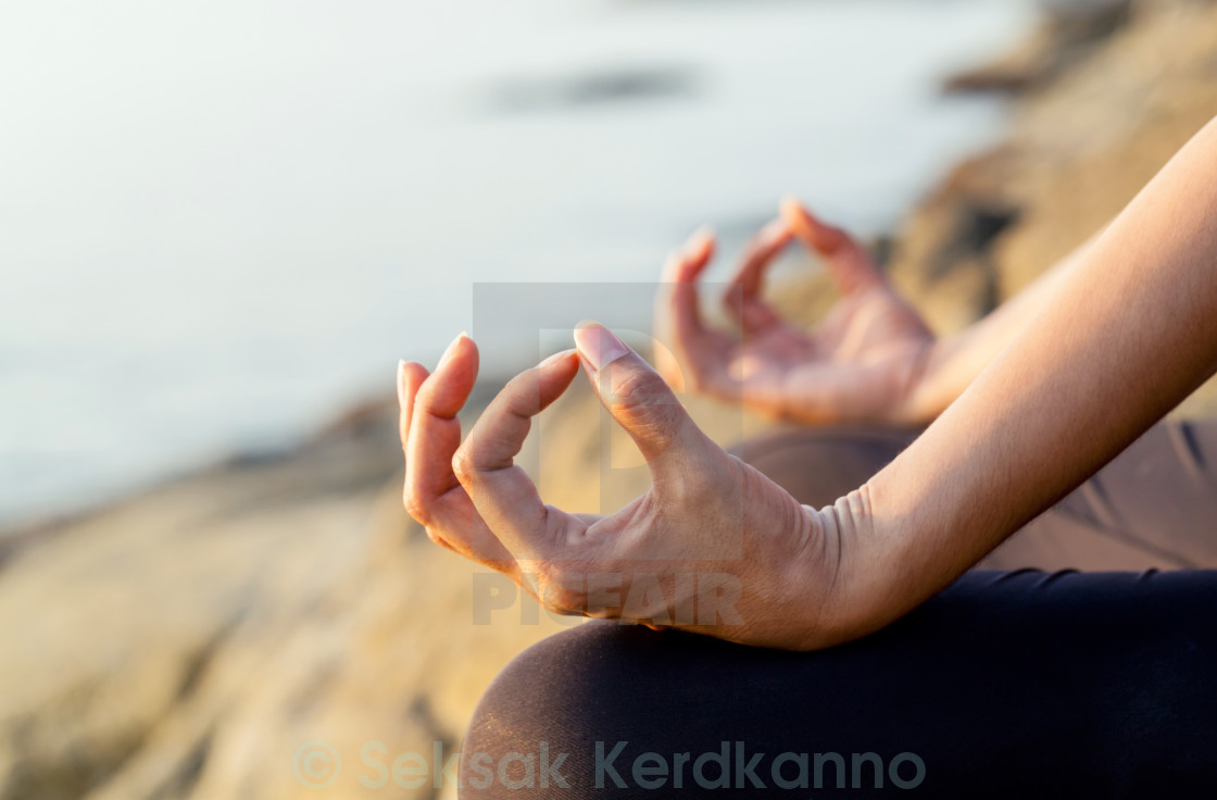 """The woman meditating in a yoga pose on the tropical beach."" stock image"