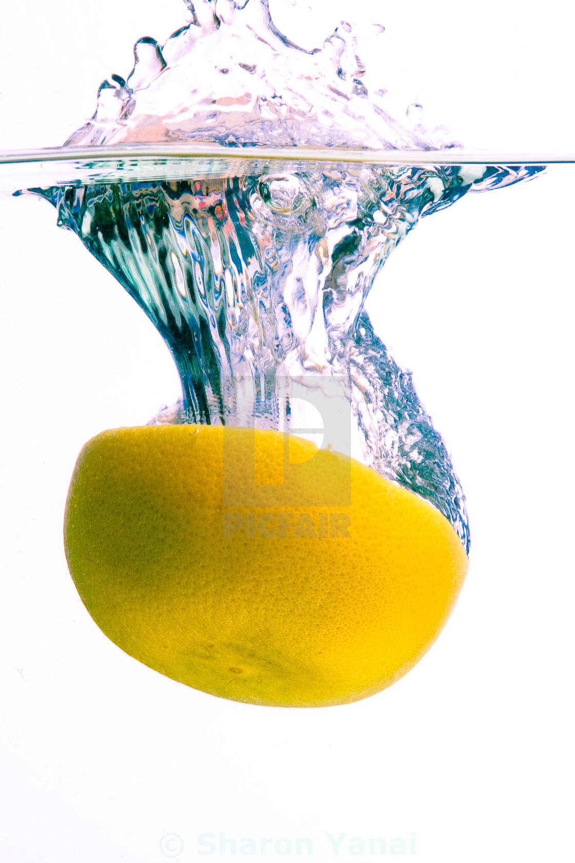 """Grapefruit falls into water with splash"" stock image"