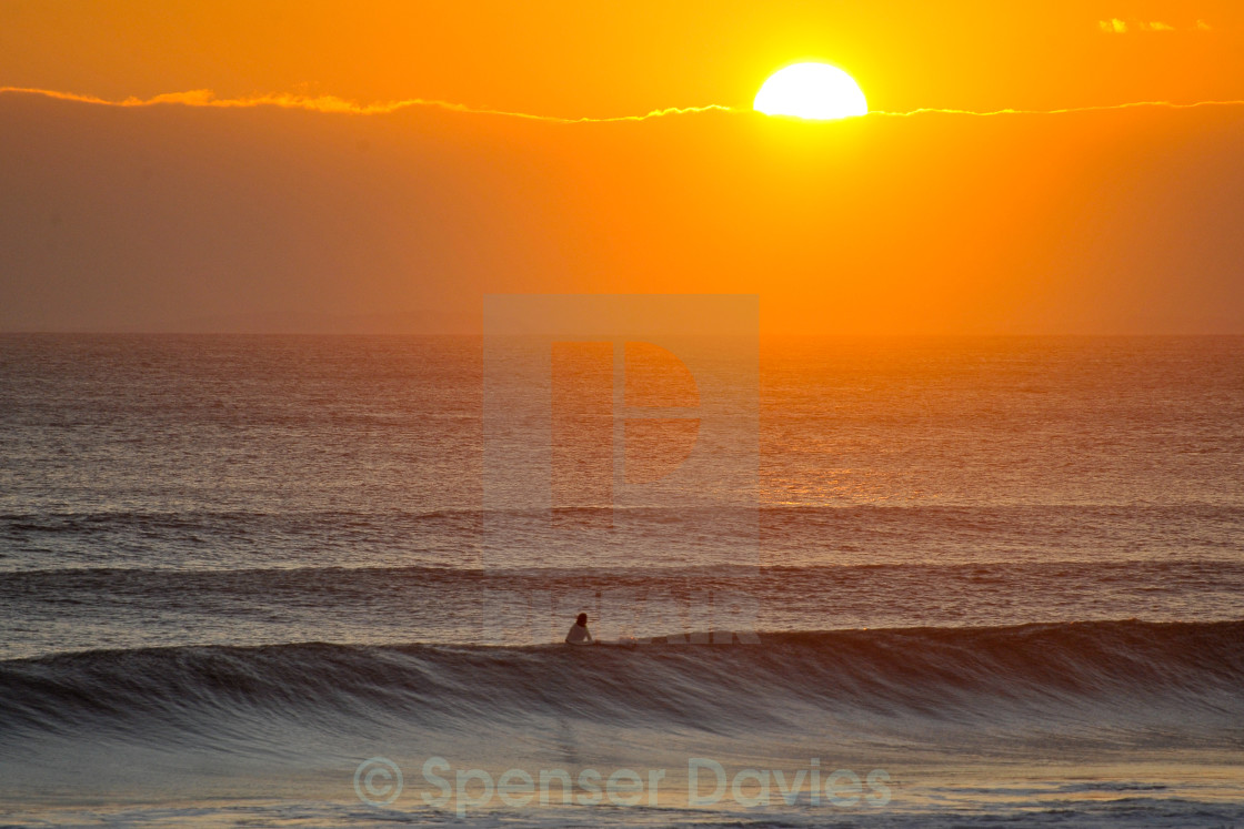 """Surfing at sunset"" stock image"