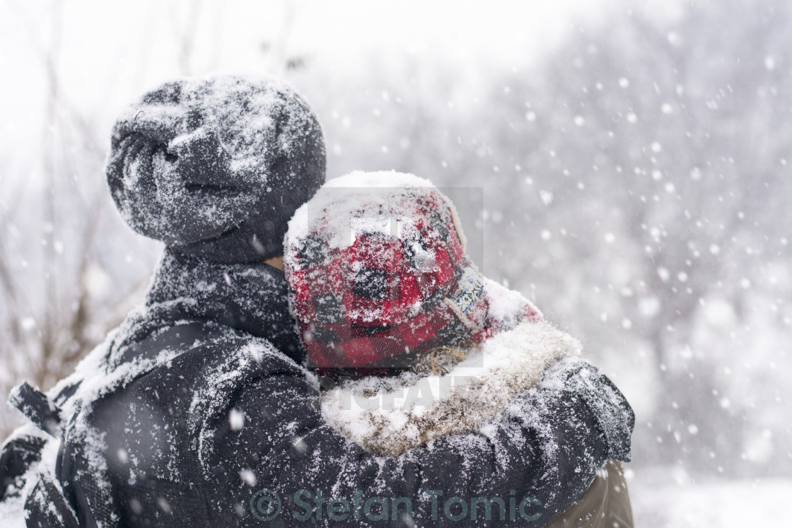 """Couple in love outdoors hugging on a winter day"" stock image"