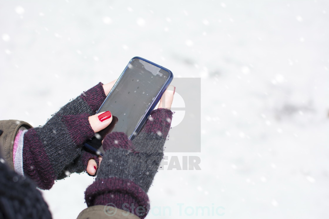 """female hands holding a cellphone outdoors in the snow"" stock image"
