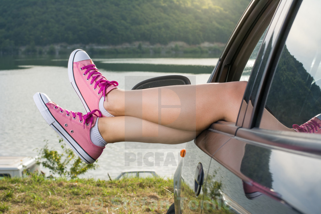 """Legs out of the car window by the lake"" stock image"
