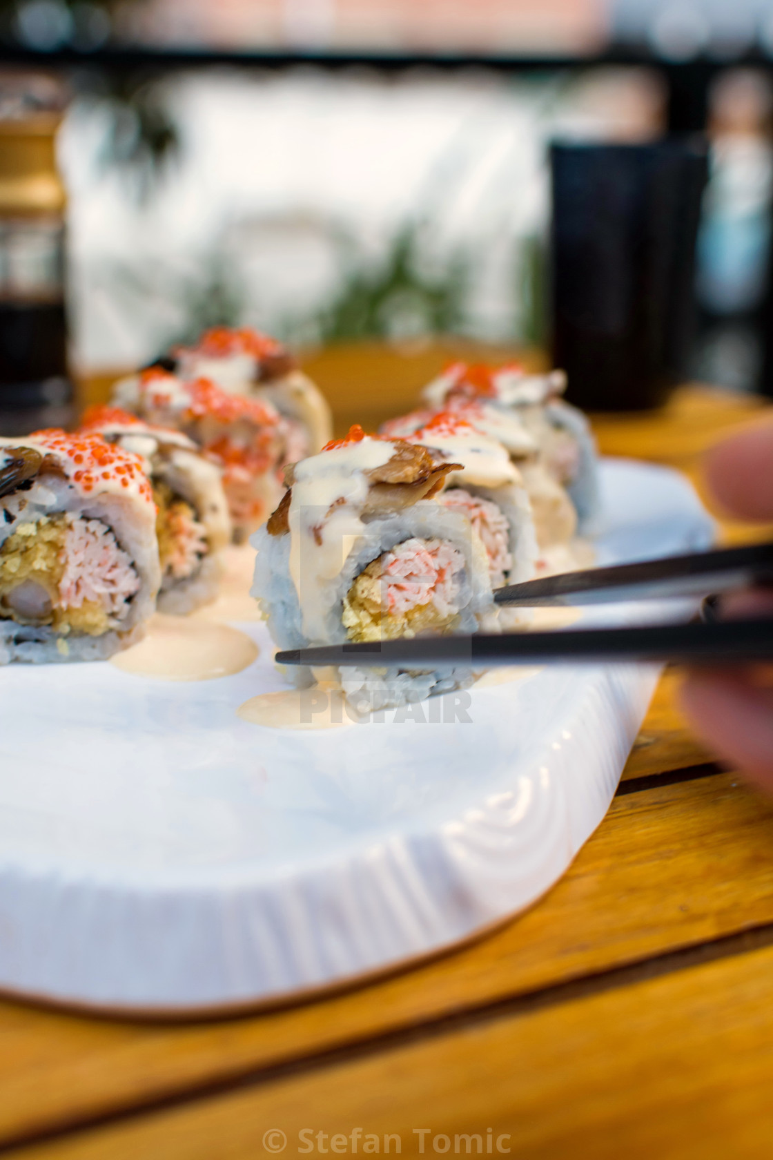 """Hand taking sushi roll with chopsticks"" stock image"