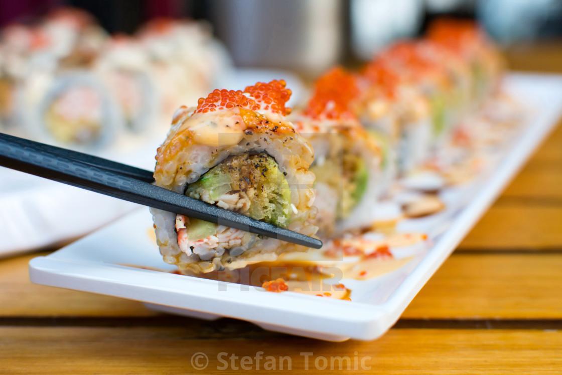 """Eating sushi rolls with chopsticks"" stock image"