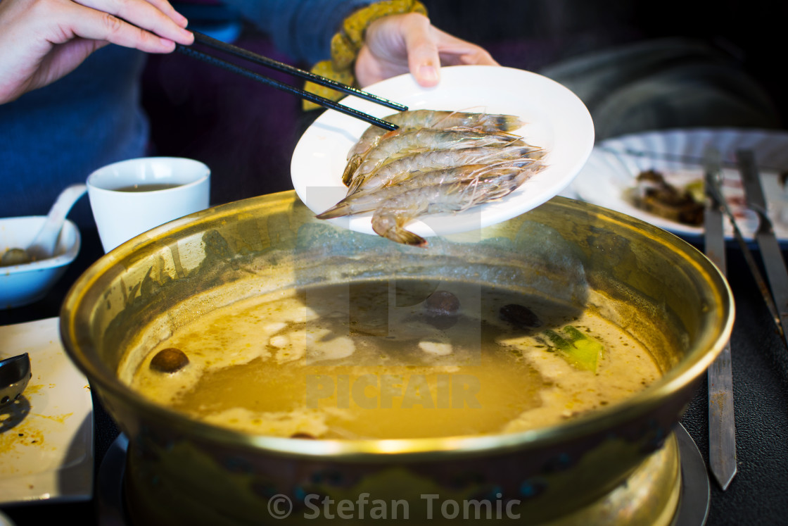 """Chopsticks inserting shrimp into hotpot"" stock image"
