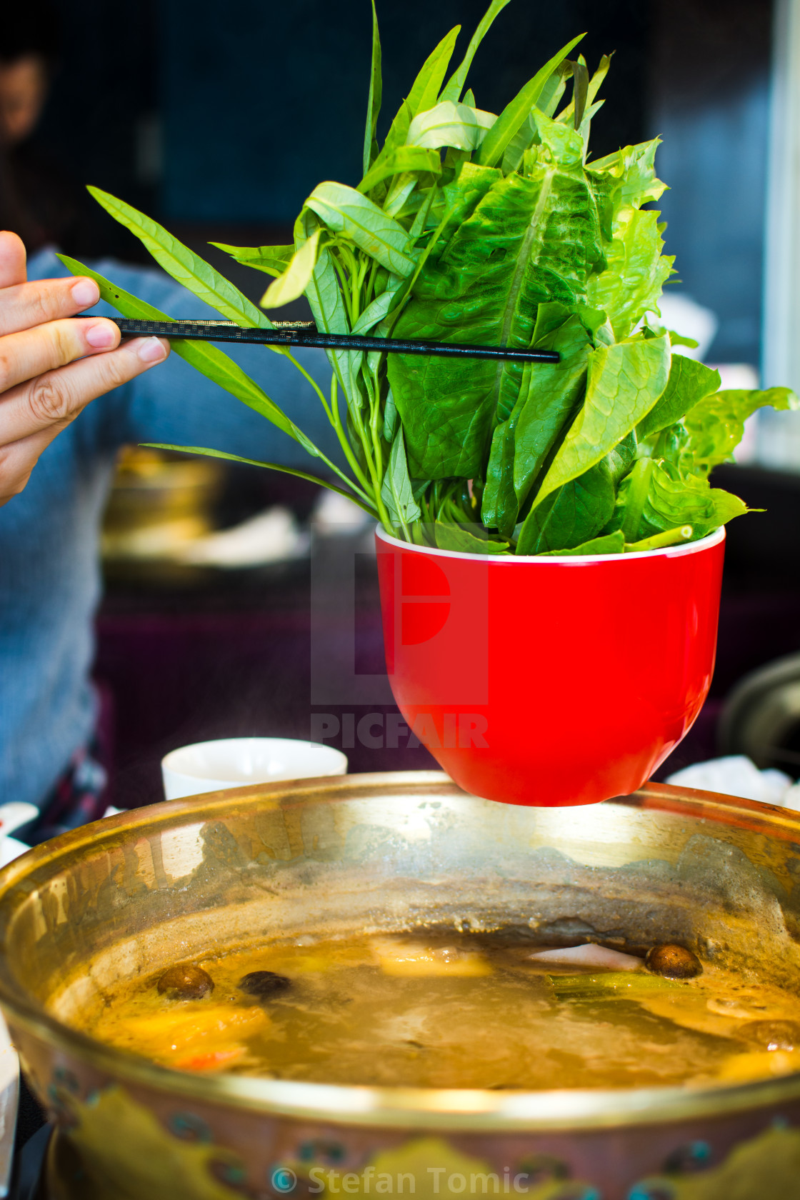 """Chopsticks inserting vegetable into hotpot"" stock image"