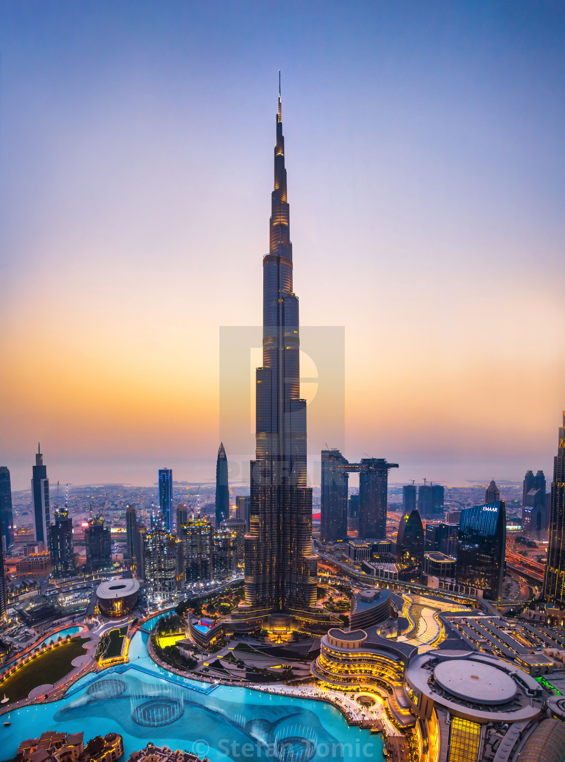 """Burj khalifa rising above Dubai mall and fountain surrounded by modern buildings top view"" stock image"