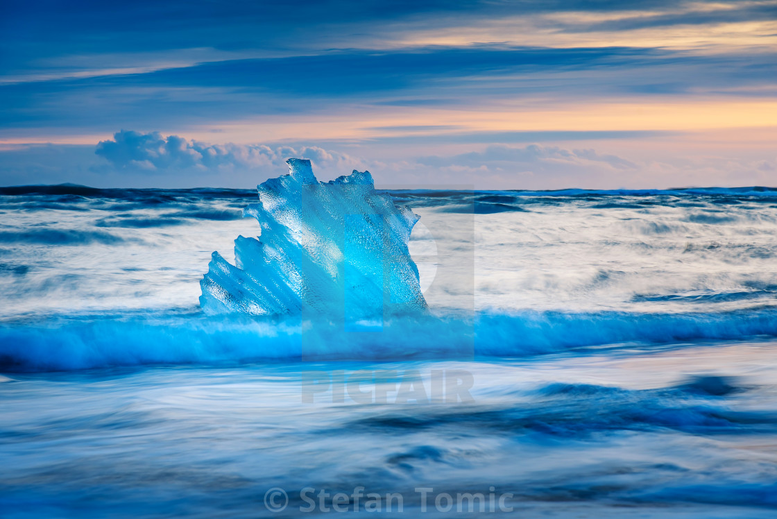 """Iceberg pieces on Diamond beach in Iceland during sunset"" stock image"