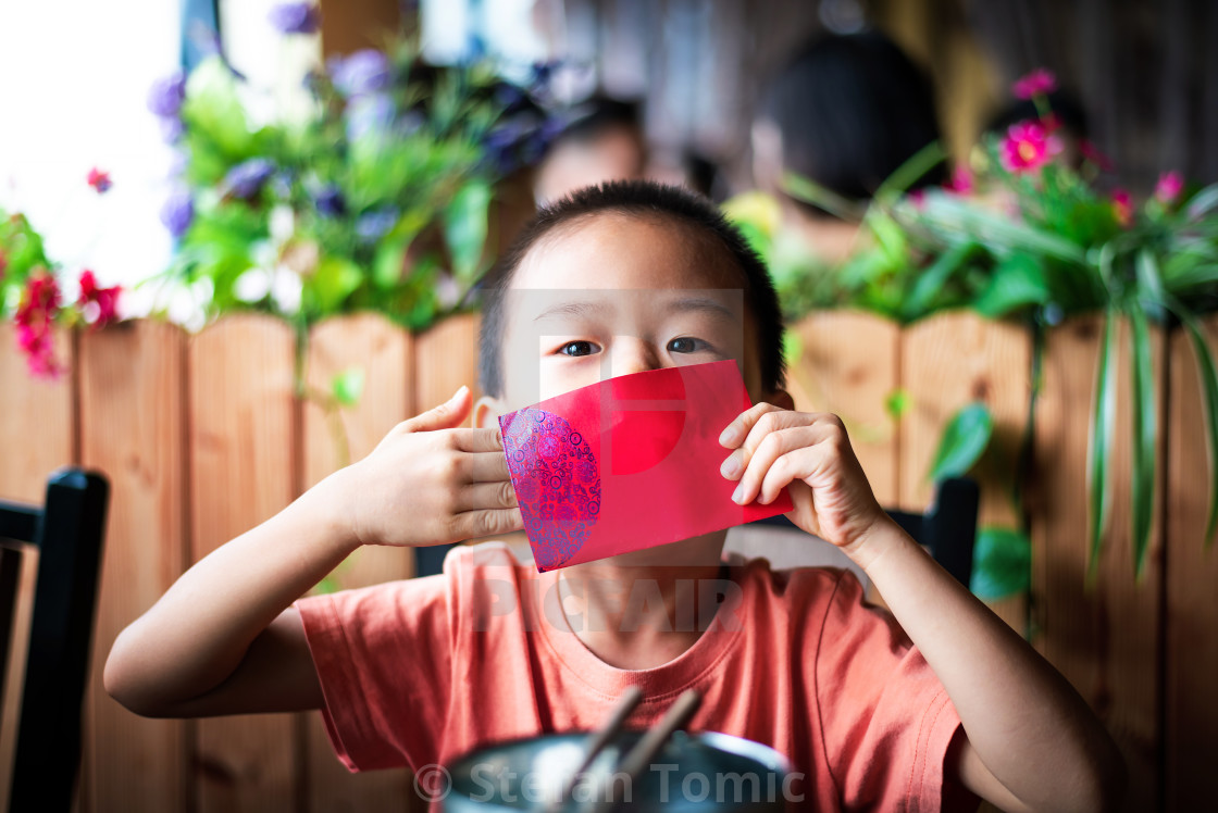 """Chinese boy receiving red pocket on the table"" stock image"