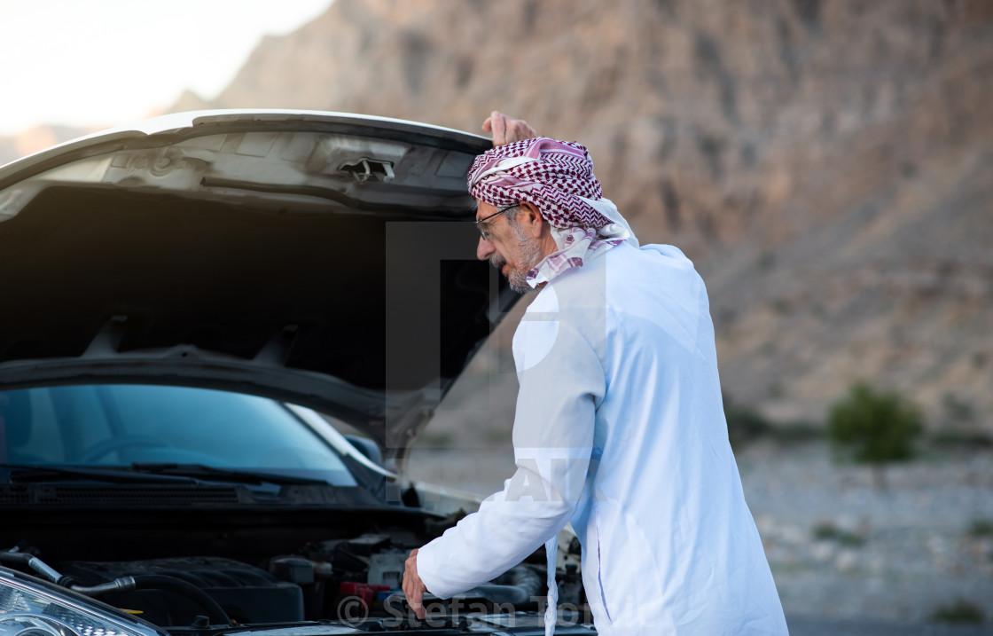 """Arab man fixing his car outdoors"" stock image"